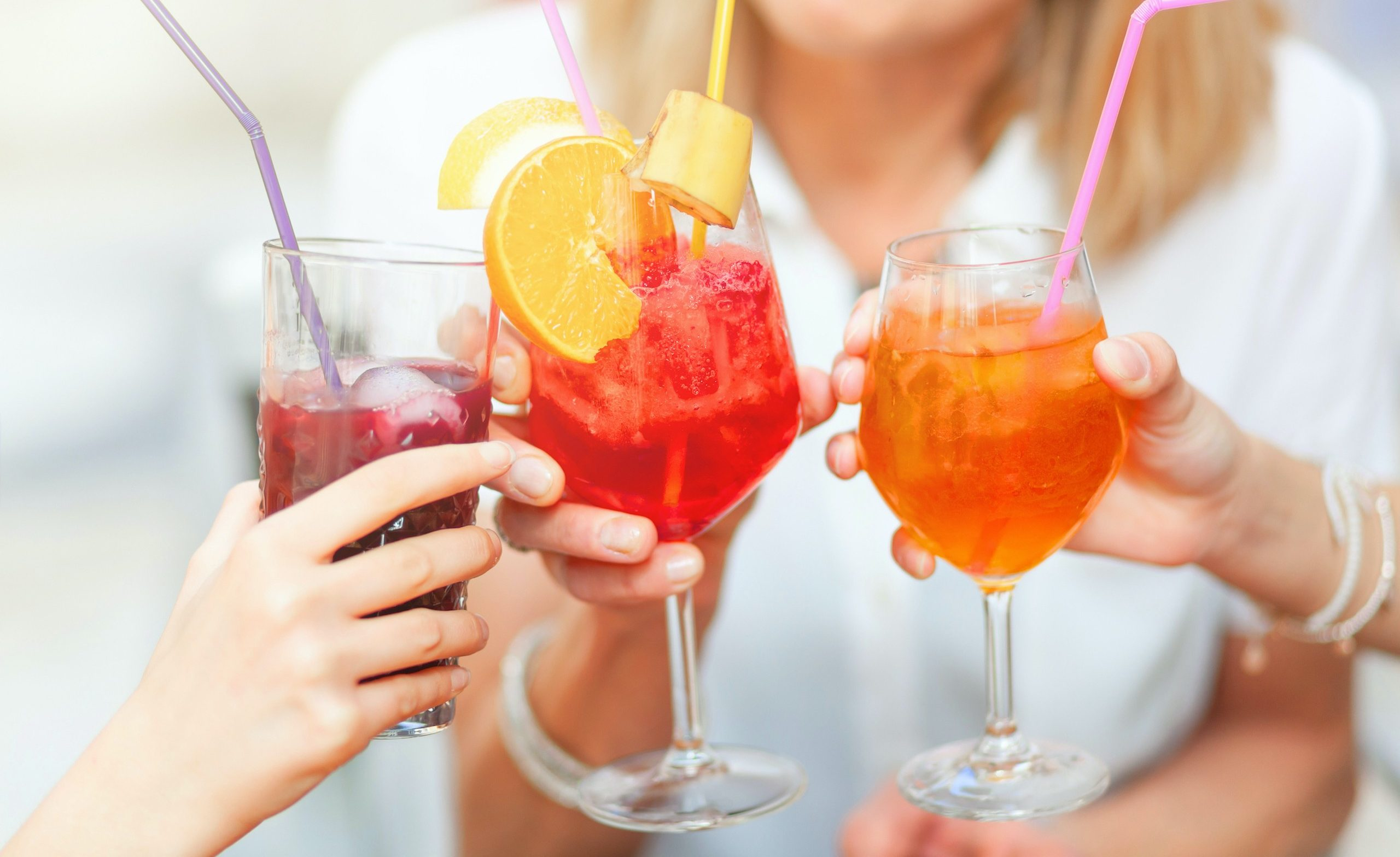Cheers with different colored cocktails, red spritz, blueberry and orange spritz.